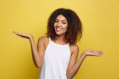 Affärsidé - stående av den härliga lugna unga afrikanska amerikanen som framlägger, genom att peka handen på sida fotografering för bildbyråer