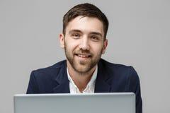 Affärsidé - stilig affärsman för stående som spelar den digitala anteckningsboken med att le den säkra framsidan Vit bakgrund Kop royaltyfri bild