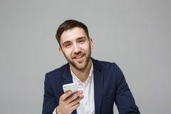 Affärsidé - stilig lycklig stilig affärsman för stående i dräkten som spelar moblietelefonen och ler med bärbara datorn på arbets royaltyfri fotografi
