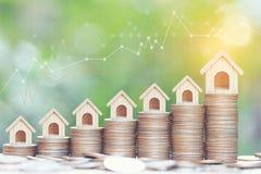 Affärsinvestering och fastighetbegrepp, växande modellhus på bunt av mynt pengar och graf på naturlig grön bakgrund royaltyfri illustrationer