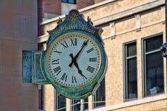 Affärsklocka som monteras på sidan av en byggnad Fotografering för Bildbyråer
