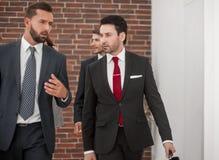 Affärskollegor diskuterar något och att promenera kontorskorridoren arkivbild