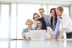 Affärskollegor med bärbara datorn som analyserar dokumentet i idérikt kontor royaltyfri bild