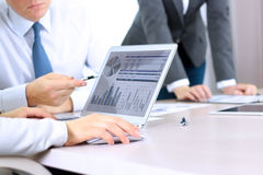 Affärskollegor som arbetar och analyserar finansiella diagram/grafer på en digital bärbar dator Arkivfoto