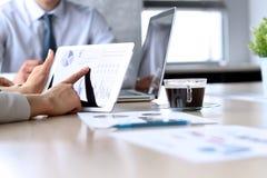 Affärskollegor som arbetar och analyserar finansiella diagram/grafer på en digital minnestavla Arkivfoton