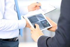 Affärskollegor som arbetar och analyserar finansiella diagram/grafer på en digital minnestavla Royaltyfri Bild