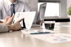 Affärskollegor som arbetar och analyserar finansiella diagram/grafer på en digital minnestavla Arkivfoto