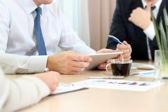 Affärskollegor som arbetar och analyserar finansiella diagram/grafer på en digital minnestavla Fotografering för Bildbyråer