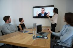 Affärskollegor som deltar i en video appell i konferensrum arkivbild