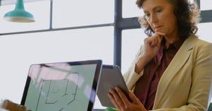 Affärskollegor som diskuterar över bärbara datorn ett skrivbord 4k stock video