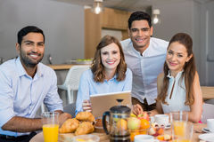 Affärskollegor som diskuterar över den digitala minnestavlan, medan ha kafeterian för frukost i regeringsställning royaltyfri foto
