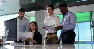 Affärskollegor som diskuterar över graf på skrivbordet 4k arkivfilmer