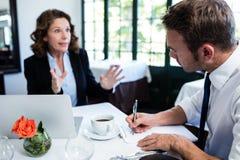 Affärskollegor som diskuterar och tar anmärkningar, medan ha ett möte Royaltyfria Bilder