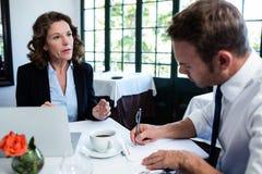 Affärskollegor som diskuterar och tar anmärkningar, medan ha ett möte Arkivbild