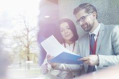 Affärskollegor som läser dokumentet, medan sitta i konventcentrum Royaltyfria Bilder