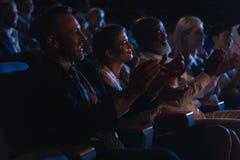 Affärskollegor som sitter och håller ögonen på presentation med åhörare och applåderar händer arkivbilder