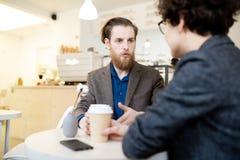 Affärskollegor som talar i coffee shop royaltyfria foton