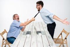 Affärskonflikt De två männen som uttrycker negativity medan en man som griper slipsen av hennes motståndare Royaltyfri Foto