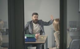 Affärskonflikt och konfrontation Ilsket framstickanderop på revisorn i regeringsställning Den skäggiga mannen och kvinnan diskute royaltyfri fotografi