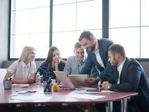 Affärskonsulenter, medan arbeta i ett lag En grupp av unga arbetare på ett möte i företagskonferensrummet royaltyfri fotografi
