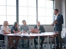 Affärskonsulenter, medan arbeta i ett lag En grupp av unga arbetare på ett möte i företagskonferensrummet royaltyfri bild