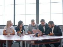 Affärskonsulenter, medan arbeta i ett lag En grupp av unga arbetare på ett möte i företagskonferensrummet arkivbild