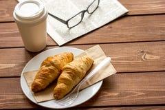 Affärskopp kaffe med croisant och tidning på skrivbordet arkivbild