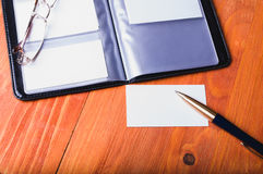 Affärskorthållare, penna på en trätabell royaltyfri foto