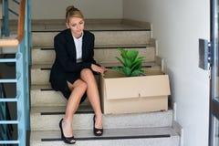 Affärskvinna With Belongings Sitting på moment på kontoret Arkivbild