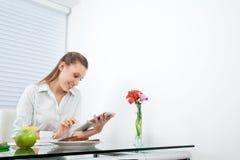 Affärskvinna At Breakfast Table som använder minnestavlaPC Royaltyfri Foto