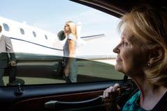 Affärskvinna In Car Looking på den privata strålen arkivbild