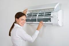 Affärskvinna Checking Air Conditioner Arkivbilder