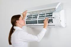 Affärskvinna Checking Air Conditioner Arkivfoto