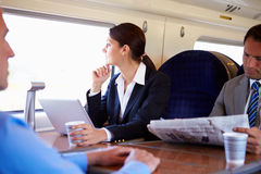 Affärskvinna Commuting To Work på drevet och användabärbara datorn arkivbild