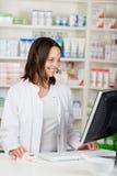 Affärskvinna Conversing On Headset i apotek royaltyfria foton