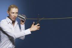 Affärskvinna Cutting Line On Tin Can String Phone royaltyfria bilder