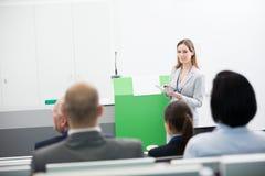 Affärskvinna With Digital Tablet som ger presentation till Audienc royaltyfria bilder