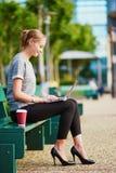 Affärskvinna eller student som utomhus dricker kaffe och arbete på hennes bärbar dator Arkivfoto