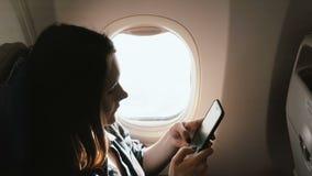 Affärskvinna för närbild för hög vinkel som ung attraktiv fokuserad Caucasian använder smartphonen som shoppar appen på flygplanf arkivfilmer