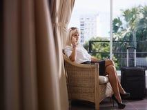 Affärskvinna genom att använda den mobila telefonen i hotellrum Royaltyfri Fotografi