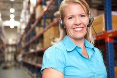 Affärskvinna genom att använda hörlurar med mikrofon i fördelningslager Arkivfoto
