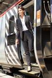 Affärskvinna Getting Off Train på plattformen royaltyfria foton