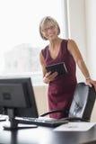 Affärskvinna Holding Digital Tablet på skrivbordet Royaltyfri Foto