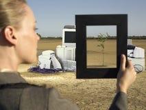 Affärskvinna Holding Plant Frame i Front Of Waste Technologies Royaltyfri Foto