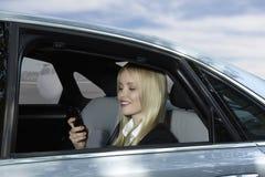 Affärskvinna i bil med mobiltelefonen på flygplatsen Royaltyfri Bild