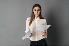 Affärskvinna i bryderiläsningdokument En isoleras på en grå bakgrund Royaltyfria Bilder