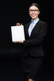 Affärskvinna i den svarta dräkten som visar den digitala minnestavlan som isoleras på svart Arkivfoto
