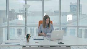 Affärskvinna i det moderna kontoret som är upptaget med skrivbordsarbete som skriver på bärbar datordatoren arkivfilmer