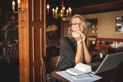 Affärskvinna i exponeringsglas inomhus med kaffe och bärbara datorn som tar anmärkningar i restaurang Arkivfoto