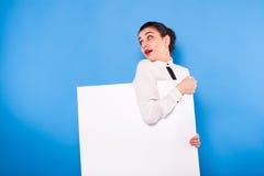 Affärskvinna i formella kläder med den vita panelen på blå backgroun royaltyfri fotografi
